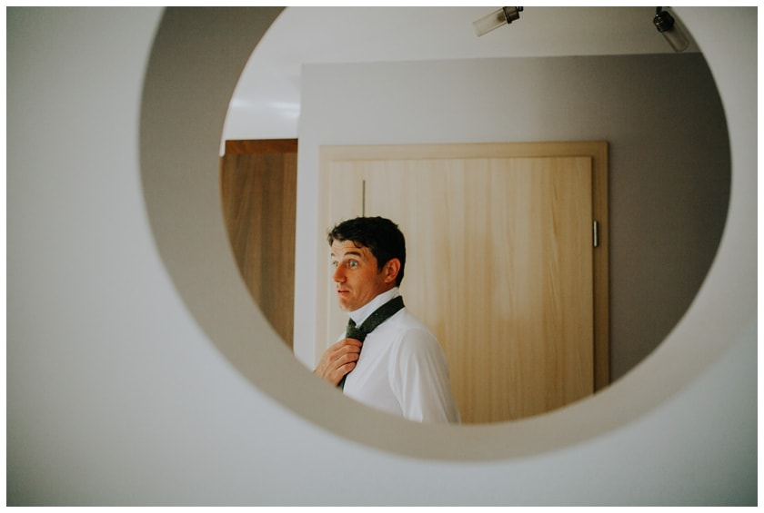 Grooms man looking surprised through a circular shaped window