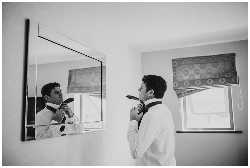 Groomsman in black and white putting on his wedding tie