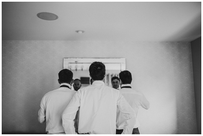 Three groomsmen shot from behind looking into the mirror as they fix their ties