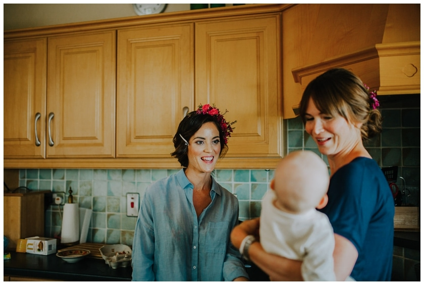 Bride smiling at her friend's baby as they stand in the kitchen
