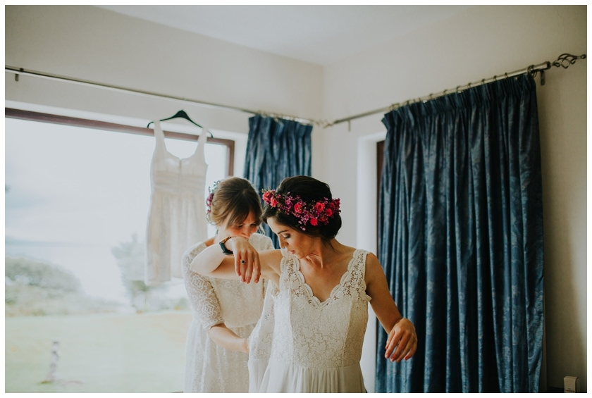 Bride getting into her dress with the help of her bridesmaid. She wears a bright pink floral crown