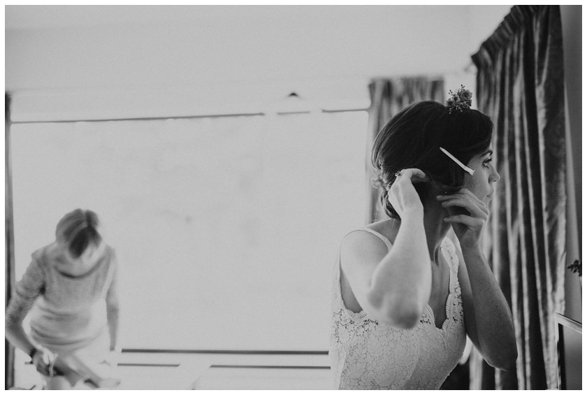 Bride fixes her hair as she looks in the mirror with her mother in the background