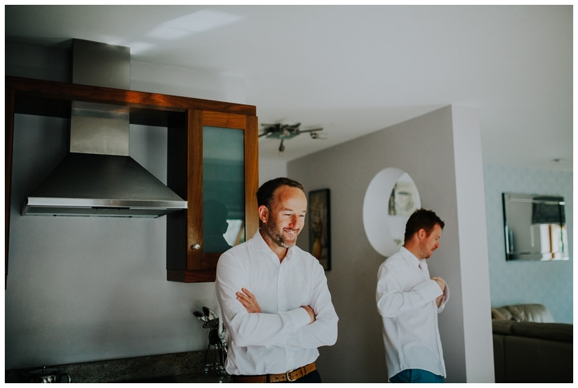 GRoom smiling standing in the kitchen with the groomsmen behind him, buttoning up his shirt
