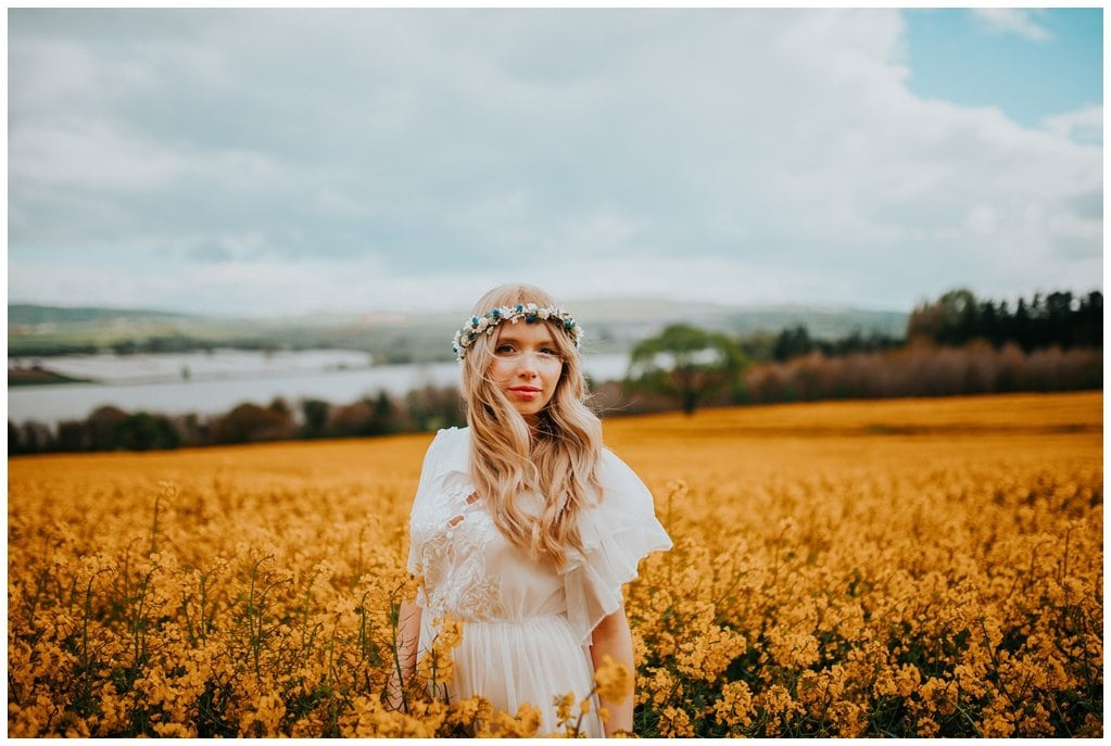 Gorgeous boho bride poses in a field in Derry wearing a vintage wedding dress