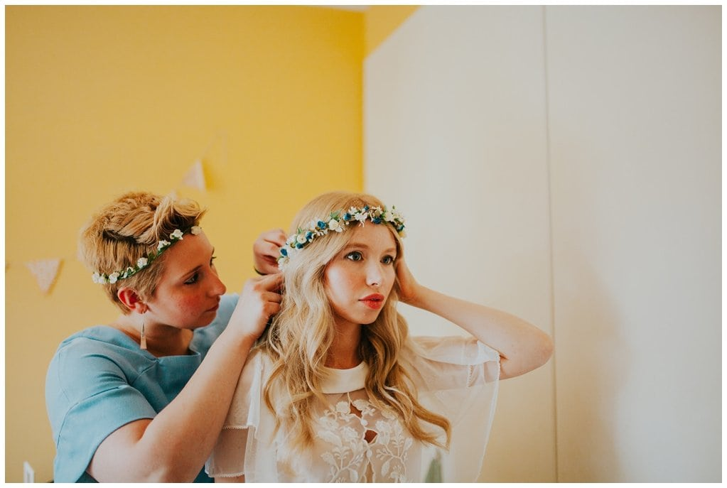 bride getting ready in her home. She wears a boho flower crown and vintage dress against a yellow wall in Derry Northern Ireland