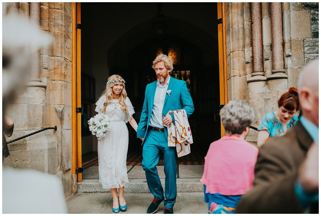 bride in vintage dress and groom in blue suit leaving the church in Strabane, Northern Ireland