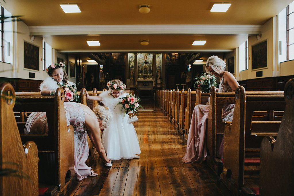 Bridesmaids and flower girls sitting on pews in Longtower chapel- derry wedding at Bishops Gate Hotel