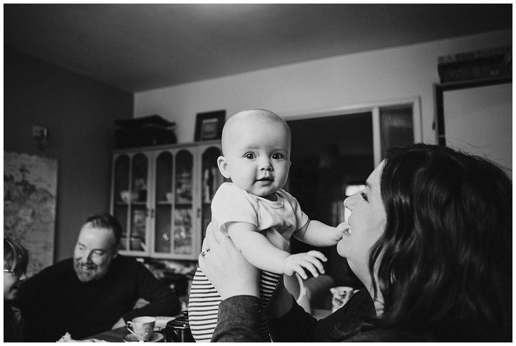 Mum holding up a smiling baby. Sitting at the dinner table- Alternative family portraits Derry