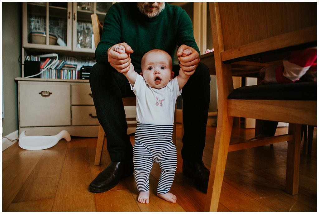 dad holding baby girl as she tries to walk - Alternative family portraits Derry