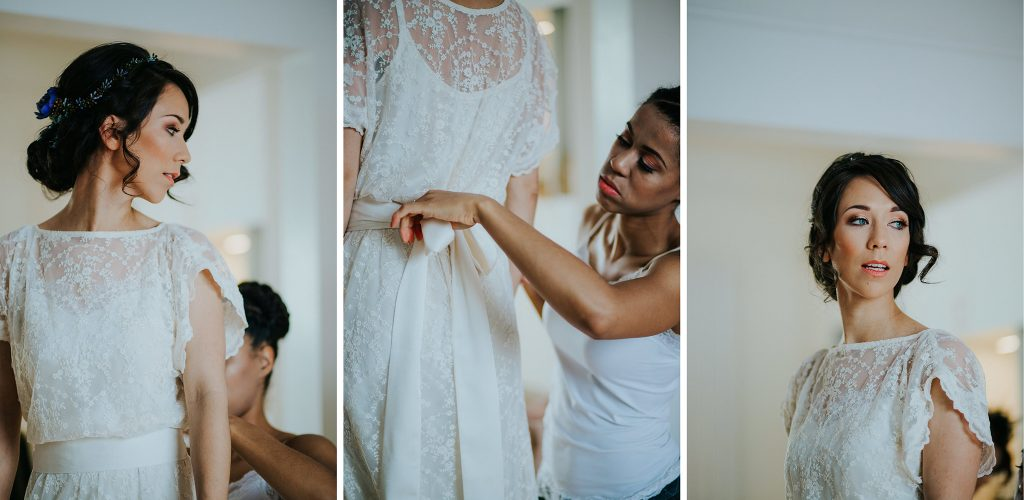 bridesmaid helping bride to tie her lace floral wedding dress by Archive 12 in Belfast
