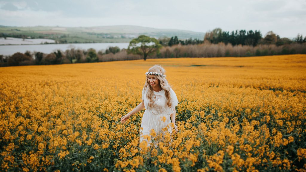 bride running through a rapeseed field in a vintage wedding dress