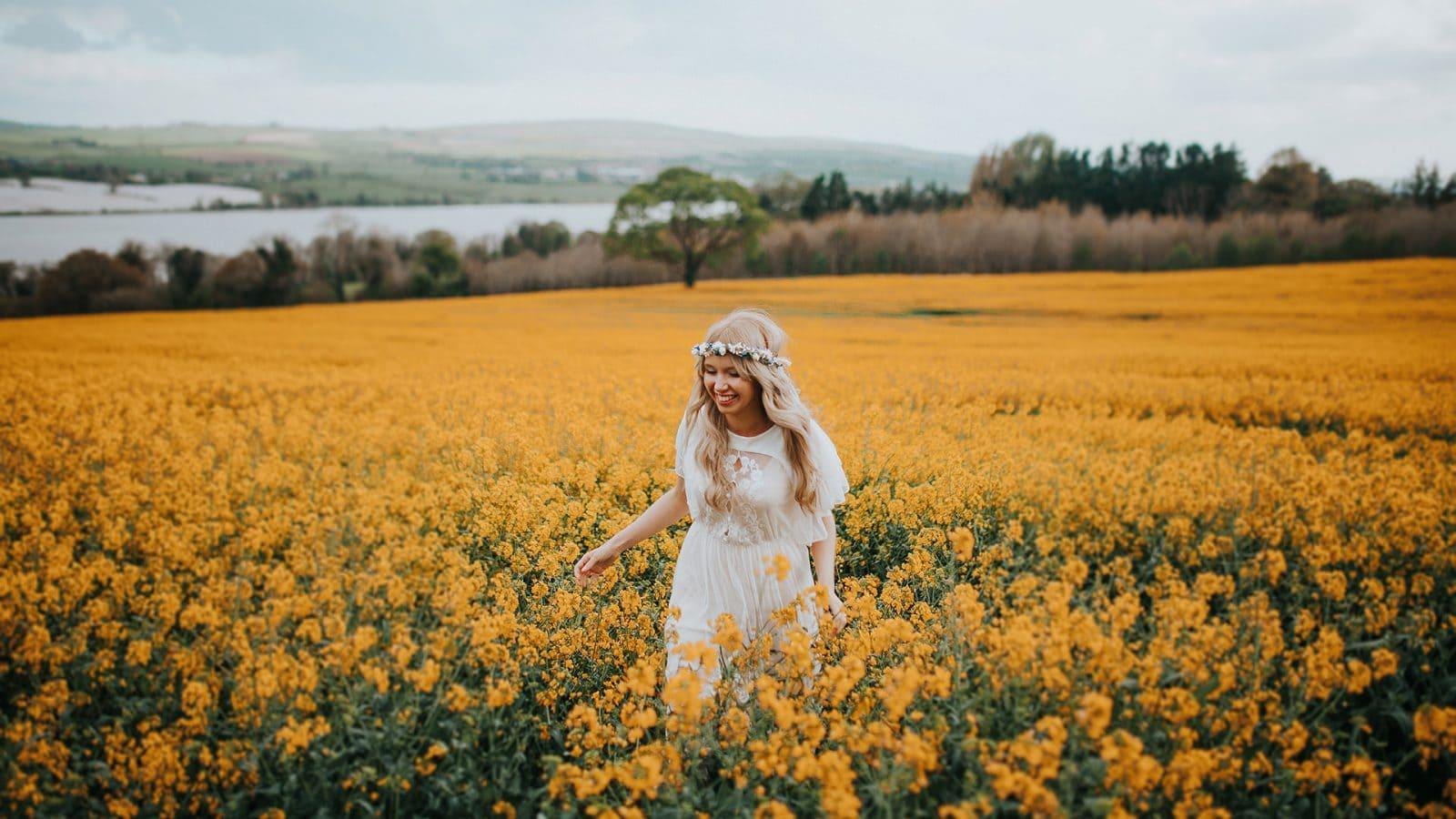 bride running through a rapeseed field in a vintage wedding dress