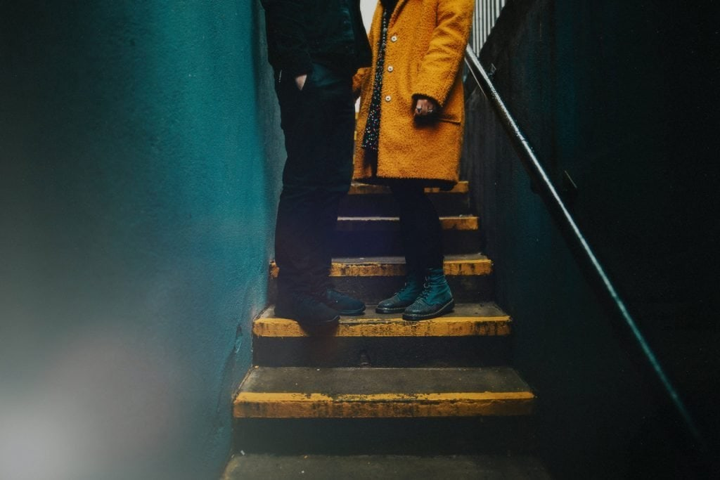 Quirky Hipster couple pose on yellow steps ahead of their wedding in Belfast. The steps have yellow strips which match the girl's coat.