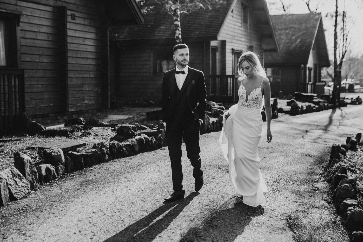 Candid black and white photo of bride and groom walking in the evening sun at Lusty beg Island