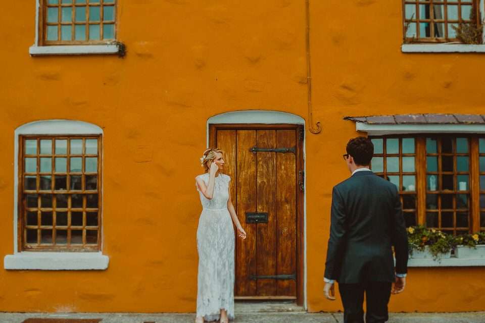bride and groom stand outside an orange house on the quay in Galway