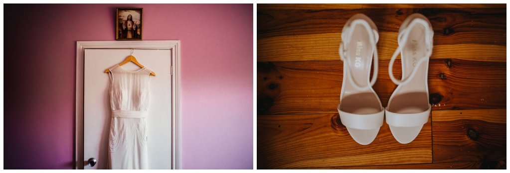 Wedding dress hangs  on door against a pink wall with wedding shoes on the floor- wedding photographers in Derry