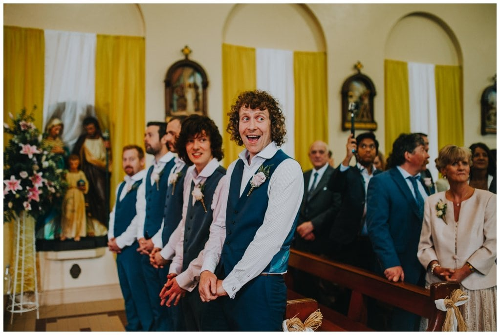 groom in church laughs as he awaits his bride