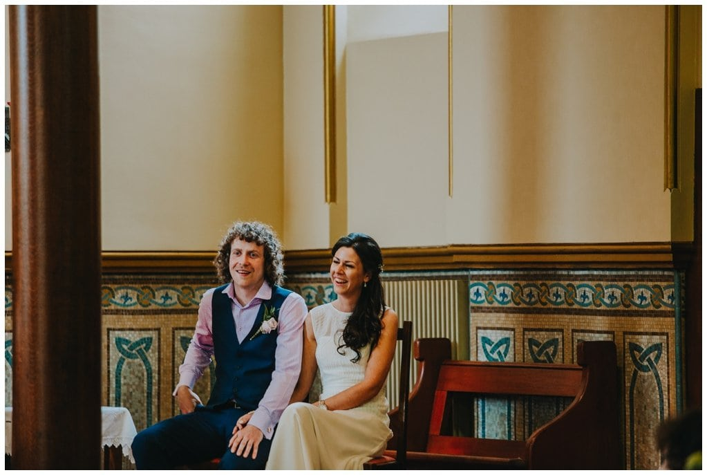 bride and groom sitting on chairs, smiling during their ceremony in Derry