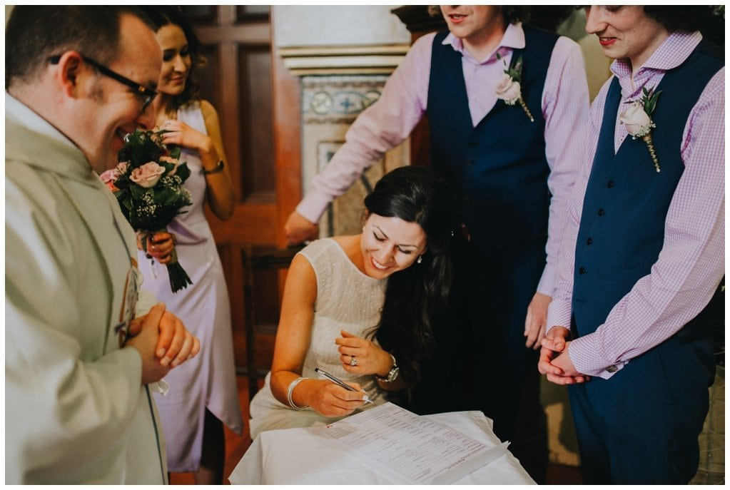 bride signs the register after marrying her husband in a church in Derry