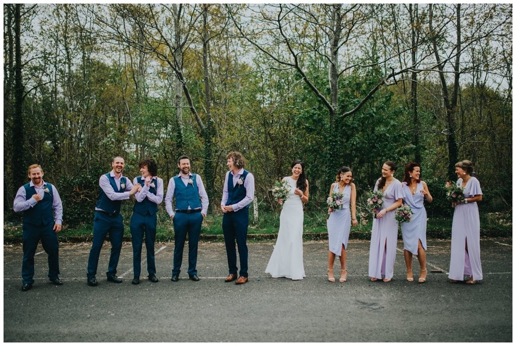 bridal party laughing as they pose for photographs against trees outside a church in Ardmore