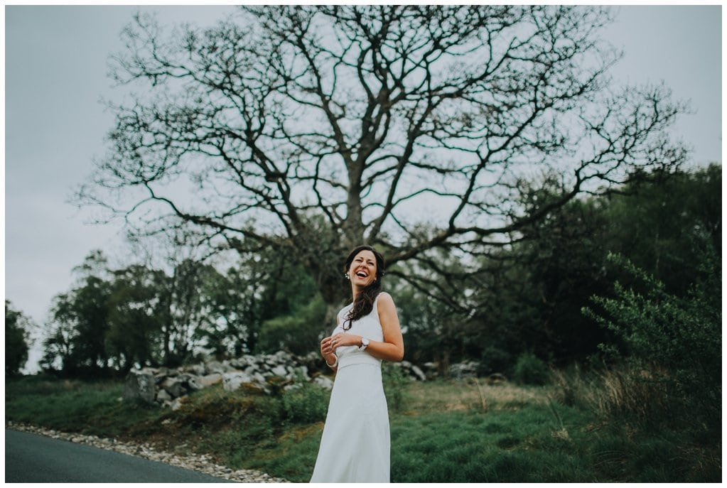 bride laughs under a tree in the Ness Woods in Derry