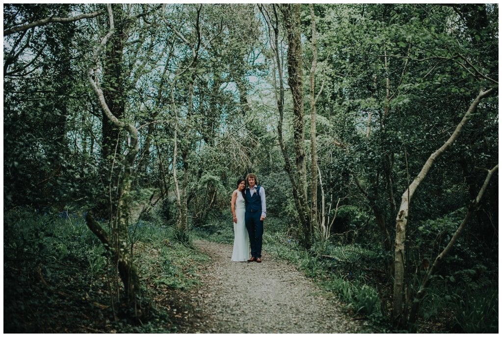bride and groom stand amidst tall trees in the Ness Woods in Derry