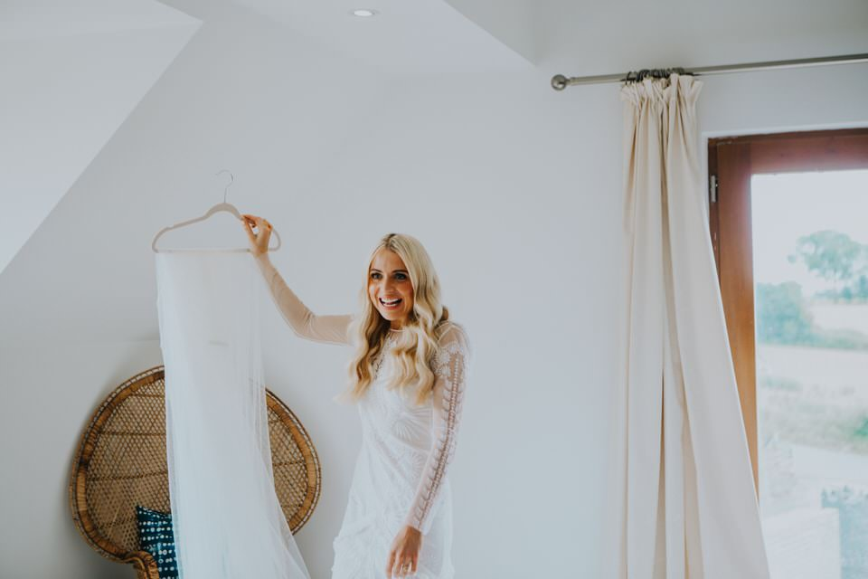 blonde bride holding up wedding veil- how to make the most of your bridal prep photos