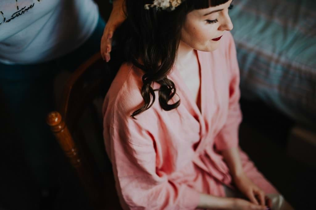 bride wearing a pink nightgown, having her hair done on her wedding day ; how to make the most of your bridal prep photos