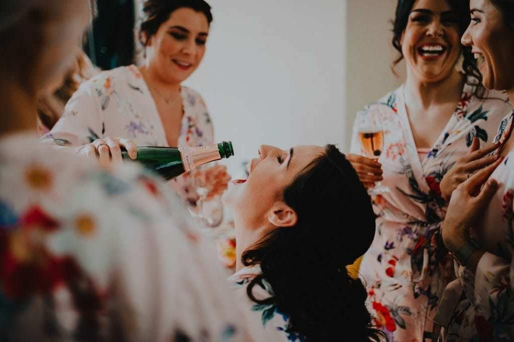 bridesmaids pouring champagne into friends mouth as they get ready for the wedding at the Millhouse in Slane - how to make the most of your bridal prep photos