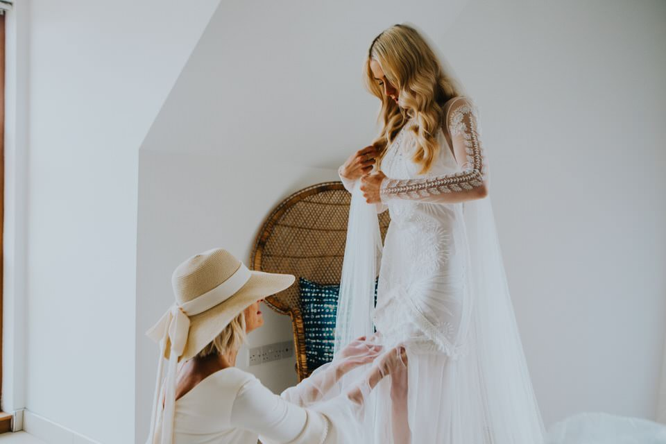 mother of the bride helping her get into her dress during bridal prep