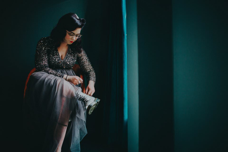 alternative bride in a black wedding dress, tying her Doc Marten Boots in moody light - how to make the most of your bridal prep photos