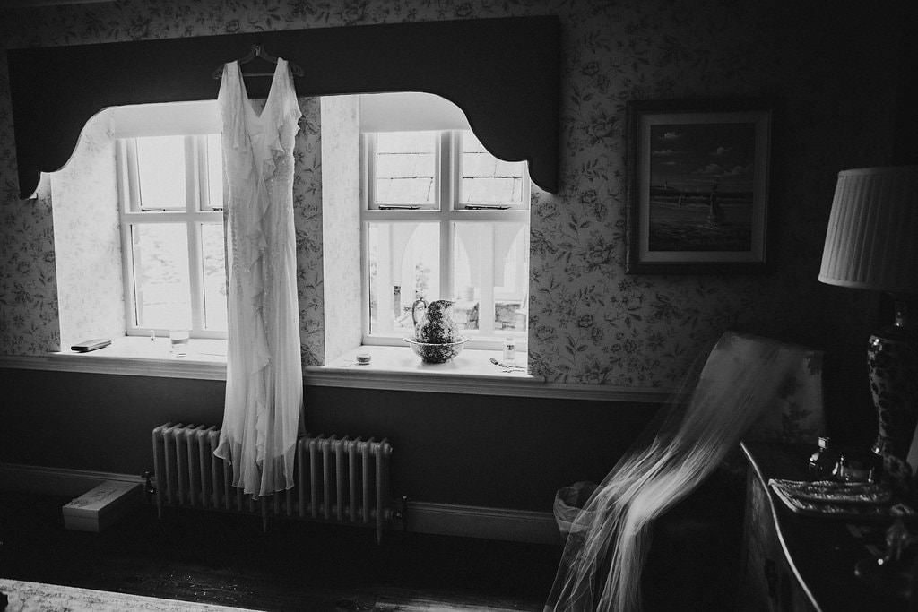 wedding dress hanging on window during bridal prep - how to make the most of your bridal prep photos