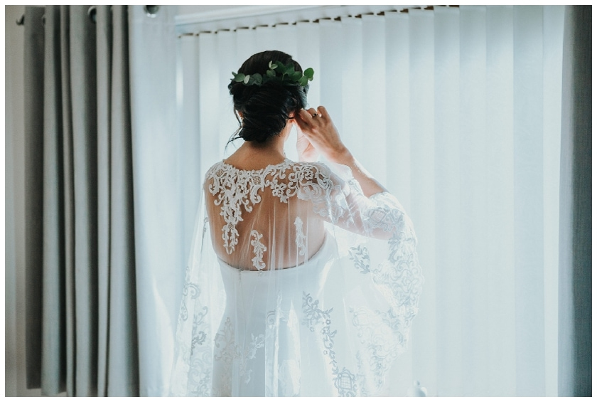 bride standing in front of window wearing wedding dress and cape by McElhinneys Bridal