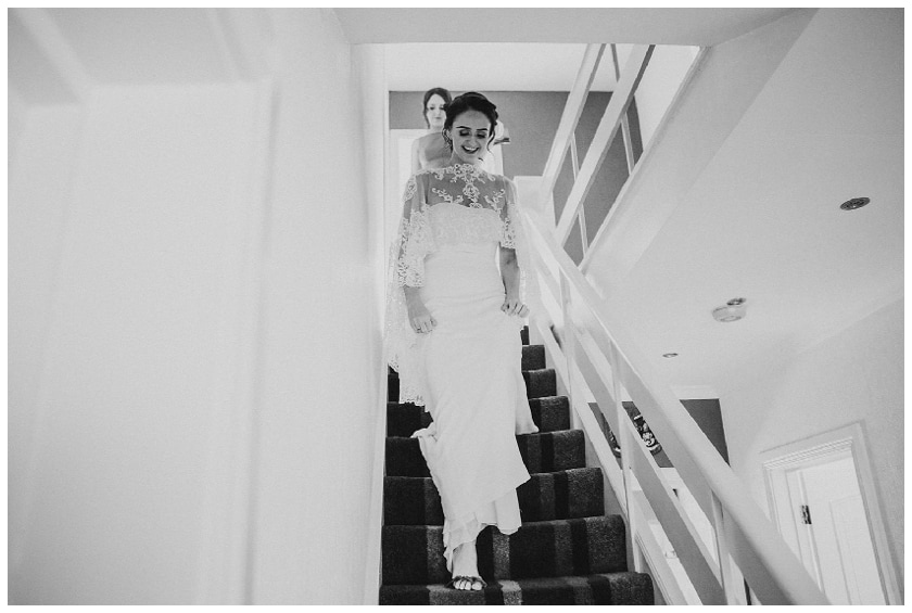 bride walking down the stairs as she gets ready to leave for the ceremony