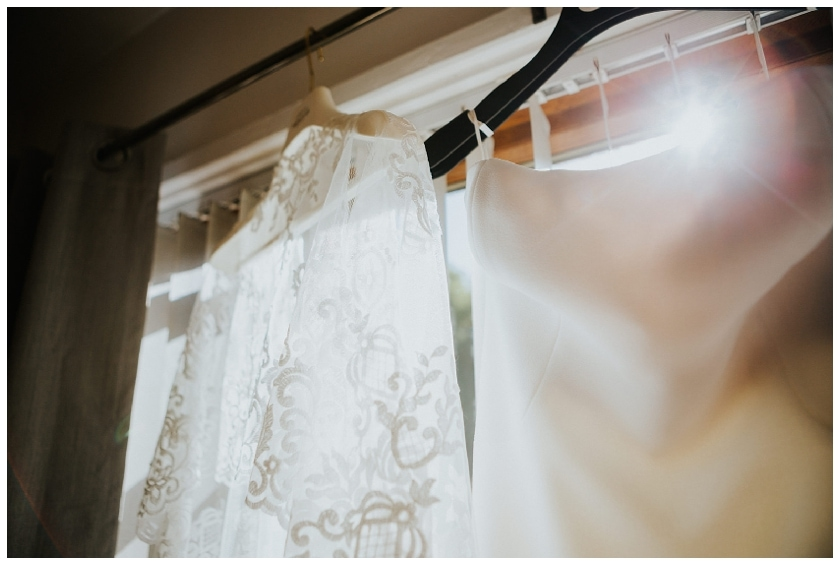 wedding dress and cape hanging on curtain rail with the sun peaking through