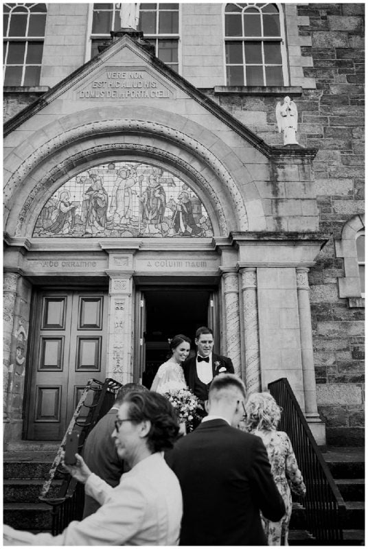newlyweds cheer as they leave Longtower chapel - wedding photographers in derry