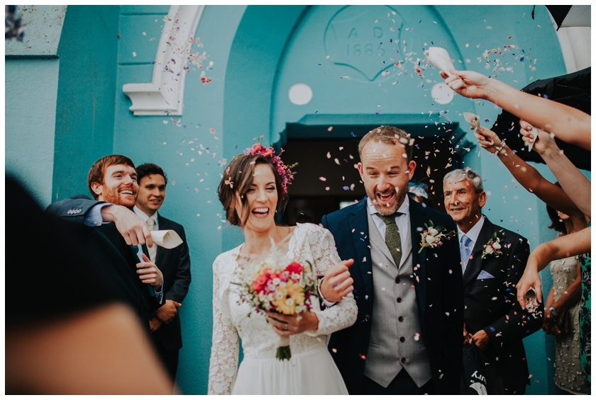 bride and groom laugh as their guests throw confetti leaving the church