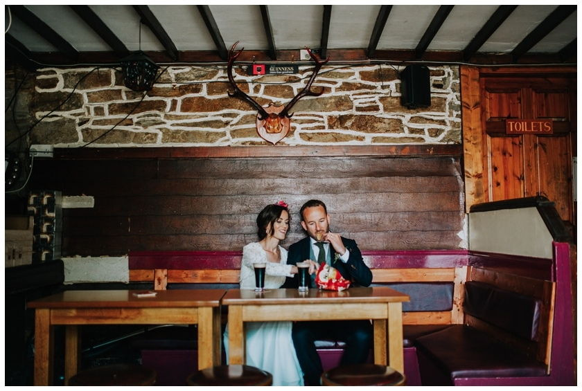 Bride and groom have a pint of Guinness underneath a stag's head in a pub in Redcastle Donegal