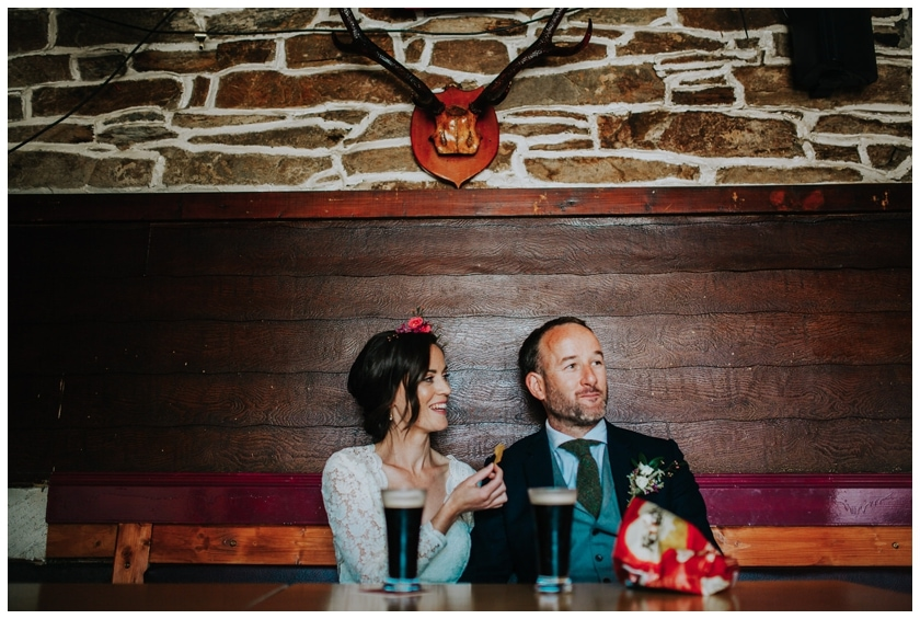 Bride and groom eat crisps underneath a stag's head in a pub in Redcastle Donegal