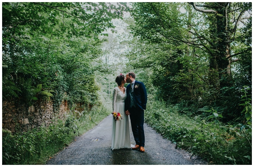 Bride and groom share a kiss surrounded by trees