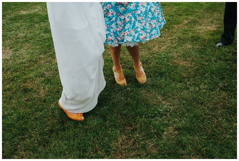 Bride and guest's feet. Guest wears bright blue dress next to the Brides mustard shoes.