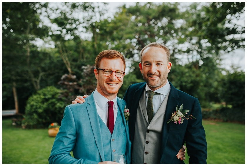 Groom poses with his best man wearing a bright blue suit and round glasses outside the red door in Fahan