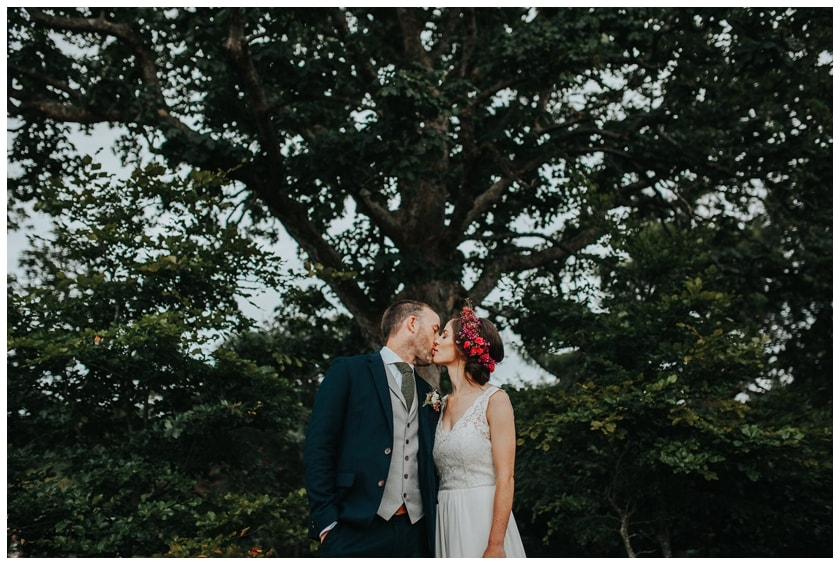 Bride and groom kissing under a tree outside the red door in Fahan. Bride wears a sleeveless lace dress with a bright pink flower crown