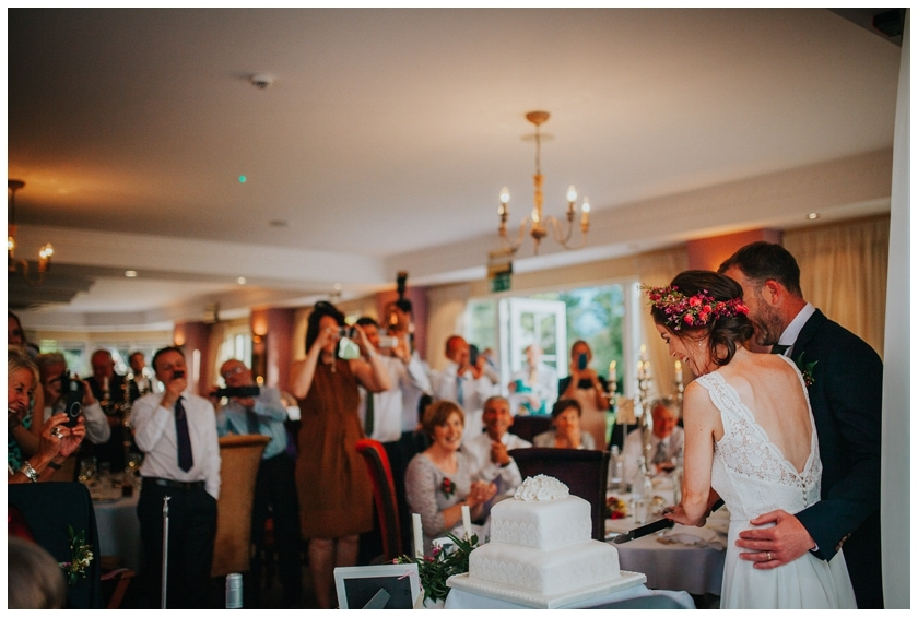 Guests photographs of bride and groom cutting the cake at the red door in Fahan