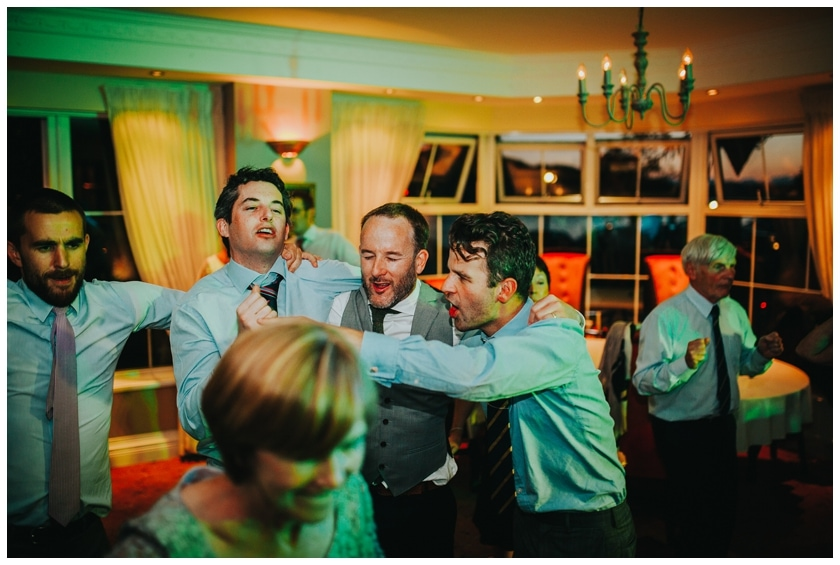 Groom and his friends dance at his wedding reception in the Red Door in Fahan