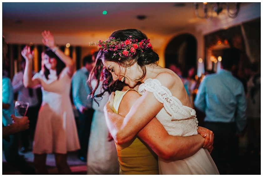 bride laughs with joy as her friend picks her up on the dancefloor at the Red Door in Fahan