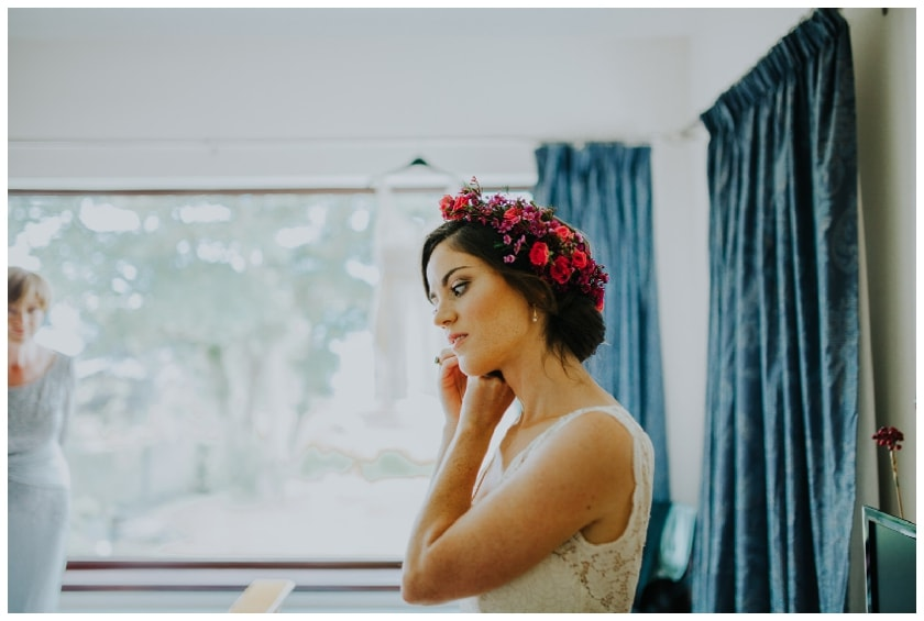 bride putting on earrings wearing a bright pink flower crown