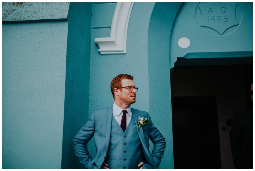 Groomsman in a blue suit against a bright the bright blue wall of Ballybrack church, waiting for the arrival of the bride