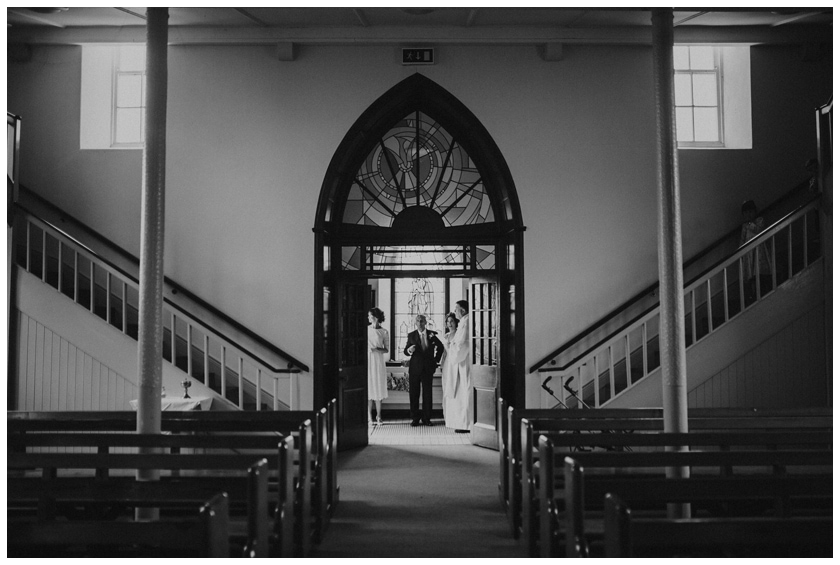 Black and white image of the back of the church with the bride and her father in the distance