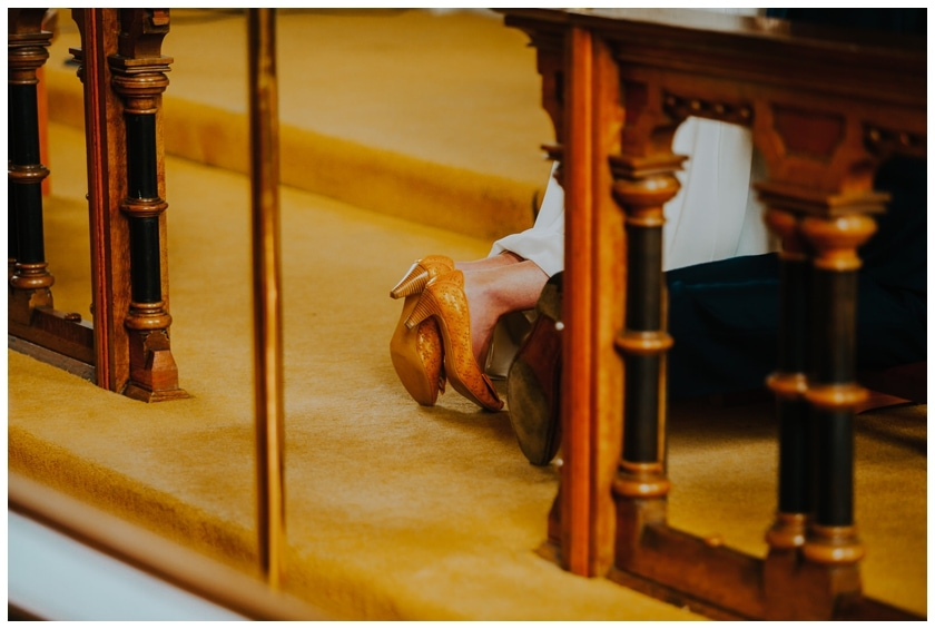bride and groom's shoes as they kneel on the altar. Carpet yellow and the Brides shoes are a mustard yellow
